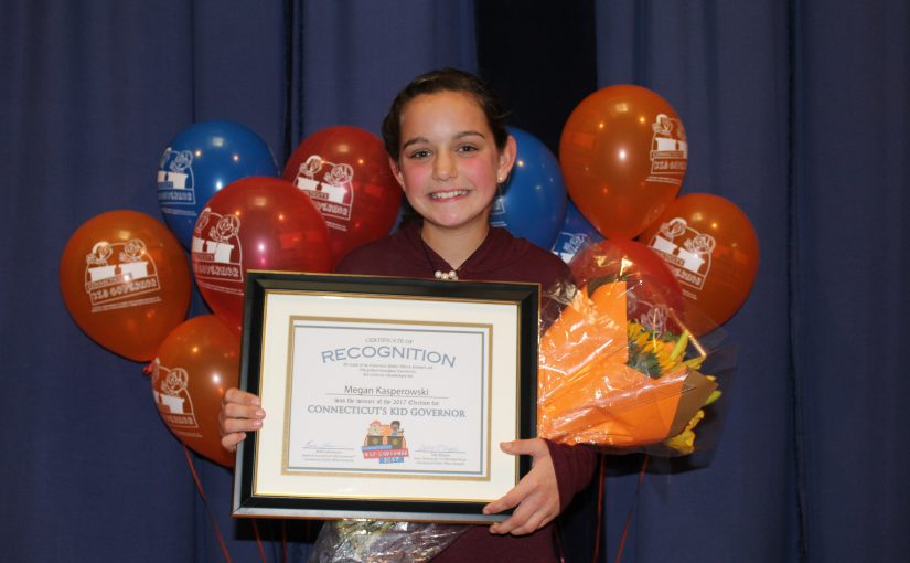 CTKG Megan stands with certificate of recognition in front of red, orange, and blue balloons.